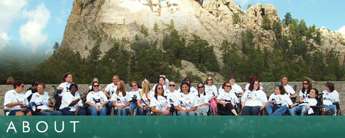 a group of Ms. Wheelchair America contestants are posing in front of Mt. Rushmore